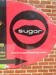 """This Way To Sugar! A red sign featuring a black circle with red lips and the word """"sugar"""" in the middle. Below is a black arrow pointing toward the store"""
